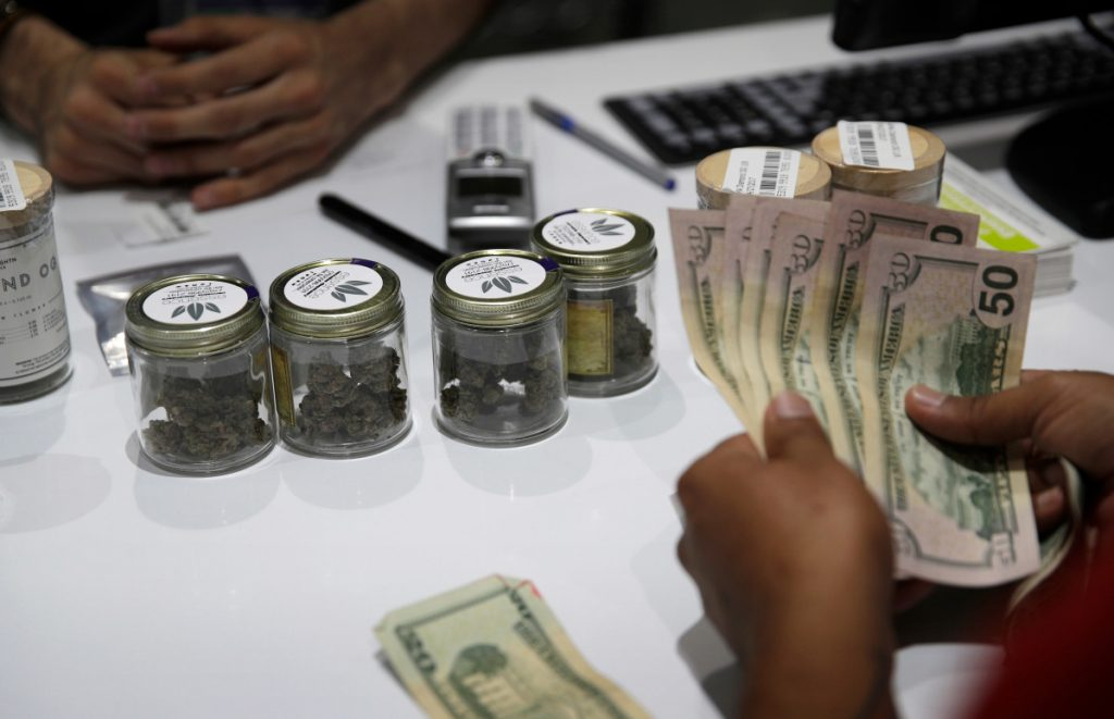 A person buys marijuana at the Essence cannabis dispensary in Las Vegas last year. Many employers across the country are quietly taking what once would have been a radical step: They're dropping marijuana from the drug tests they require of prospective employees.