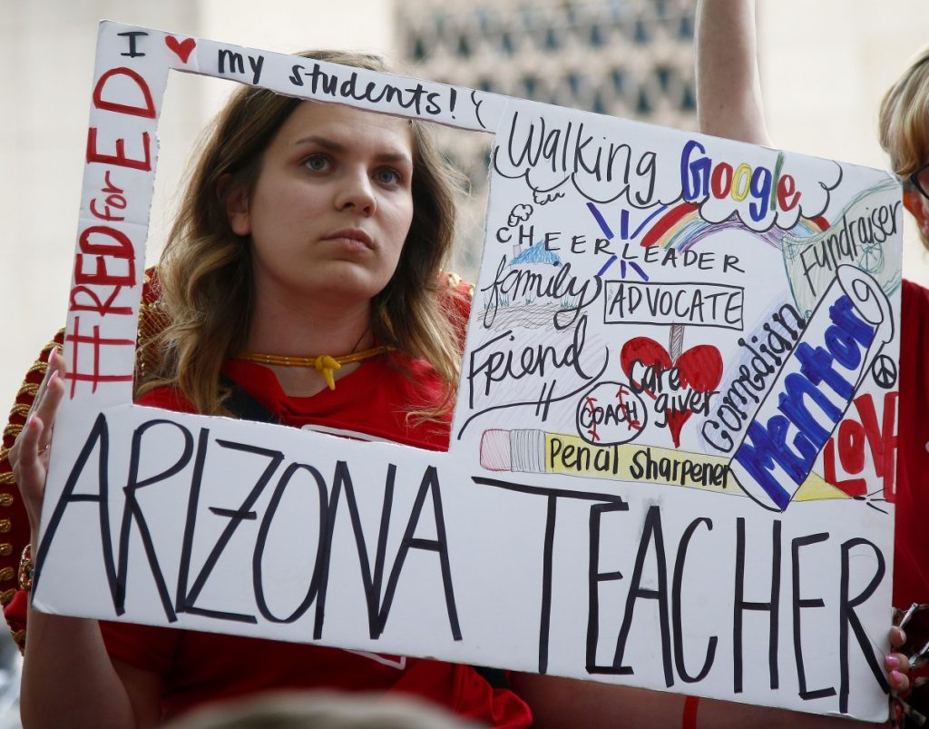 Teacher Taylor Dutro listens as protest organizers announce Arizona teachers' intentions to go back to work if lawmakers pass a school funding plan, during the fourth day of the statewide teachers' strike at the Arizona Capitol on Tuesday in Phoenix. Associated Press/Ross D. Franklin