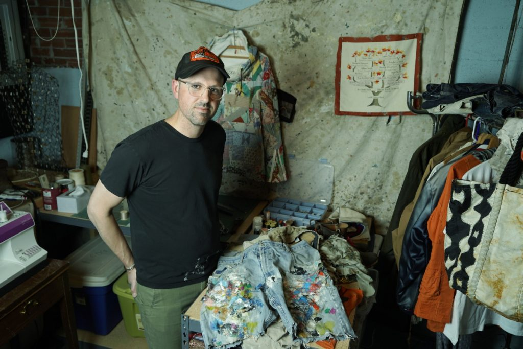 Jared DeSimio in the basement workspace at his home. DeSimio creates one-of-a-kind clothing from old garments, and also mends clothes, like the shorts of an artist friend of his seen on the table in the foreground.
