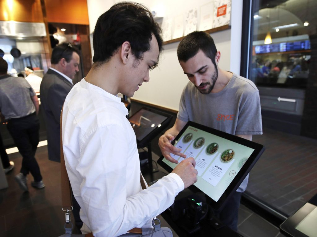 Charles Renwick, right, lead software engineer at Spyce Food Co., assists a customer with an order at the Spyce restaurant. It was founded by four former MIT classmates who partnered with Michelin-starred chef Daniel Boulud.