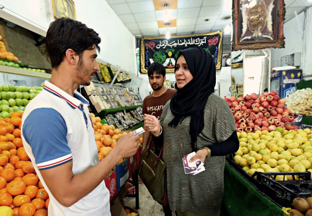 Sahira Falih, a candidate for parliamentary elections, speaks with a vegetable seller as she campaigns in April at a market in Baghdad, Iraq.  Women candidates face many challenges.