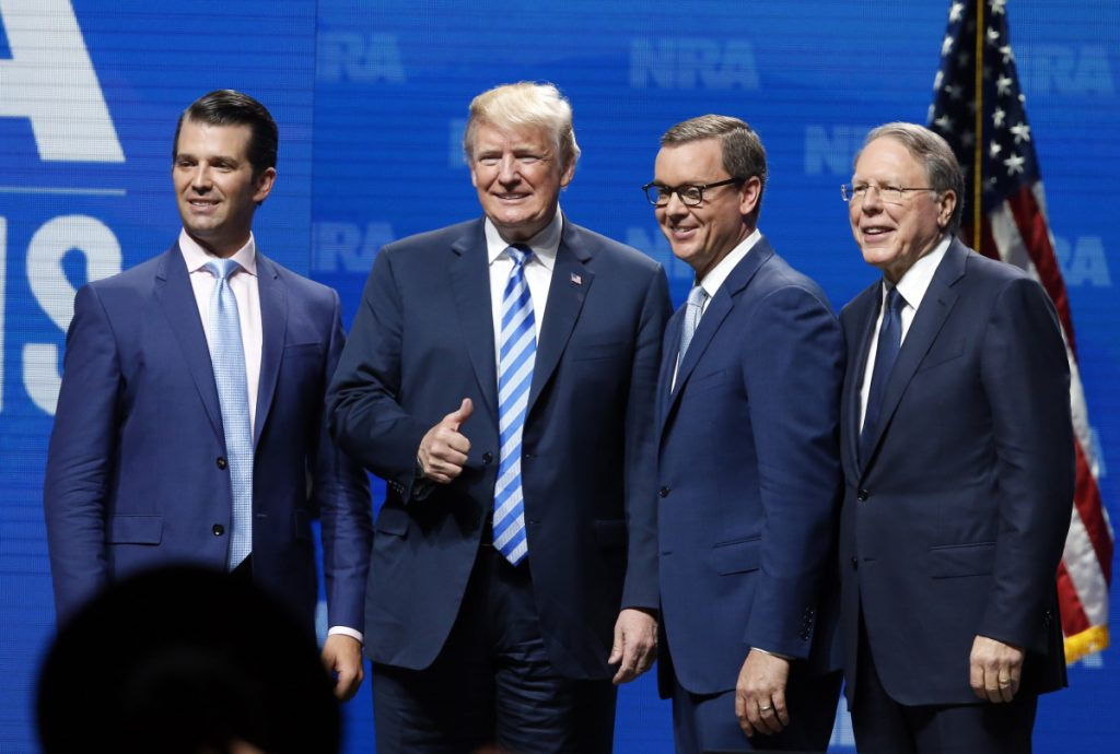 Donald Trump Jr., from left, President Trump, Chris Cox, executive director of the National Rifle Association-Institute for Legislative Action Leadership Forum and NRA executive vice president Wayne LaPierre, right, stand on stage at the NRA meeting in Dallas on Friday.