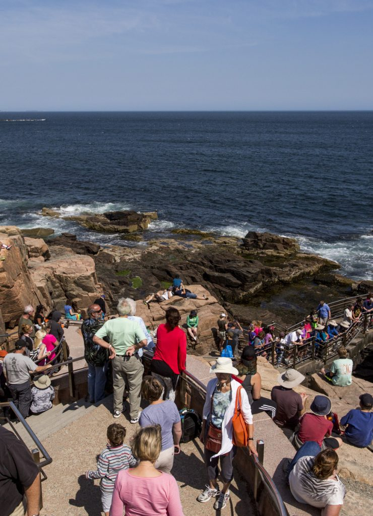 Tourists flock to Thunder Hole at Acadia National Park, where famous waves crash against the rocks. Public input is being sought on four different proposals to better manage park traffic and crowds.