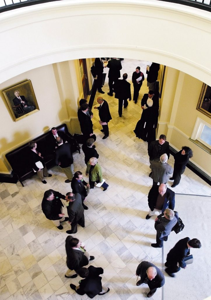 Lobbyists wait for lawmakers between the houses of the Legislature in Augusta. The private-interest lobby is more powerful because of legislators' term limits, a writer says.