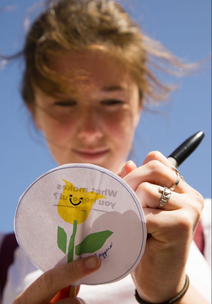Anna Friberg, 18, of Cape Elizabeth writes a message on a paper marker as part of the Yellow Tulip Project last May 7 in Portland's Lincoln Park. Sunday's gathering is meant to be a time for celebration, with hope for those who are struggling.
