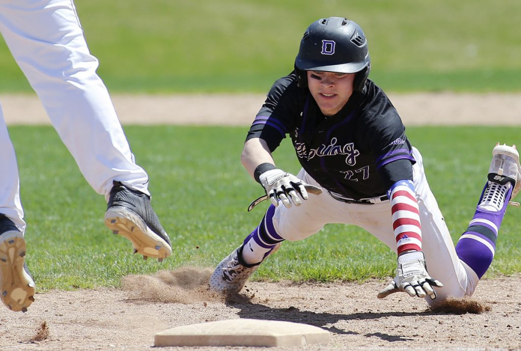 Jack Lynch of Deering dives safely back to first base as Westbrook's Jack Stone leaps for a pickoff attempt by pitcher Destin Delponte.