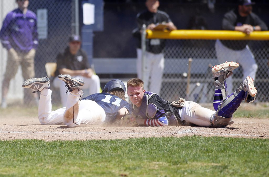 Westbrook's Maxim Dobkowski is safe at home after colliding with Deering catcher Jack Lynch during an SMAA baseball game Saturday in Westbrook. Deering won, 16-8.
