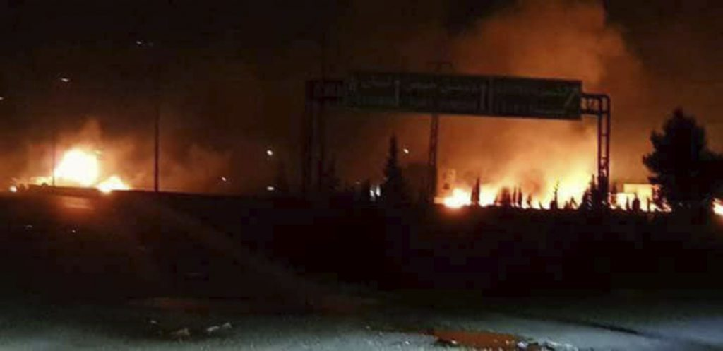 This photo released Wednesday by the Syrian official news agency SANA shows flames rising after an attack in an area known to have numerous Syrian army military bases, in Kisweh, south of Damascus, Syria.