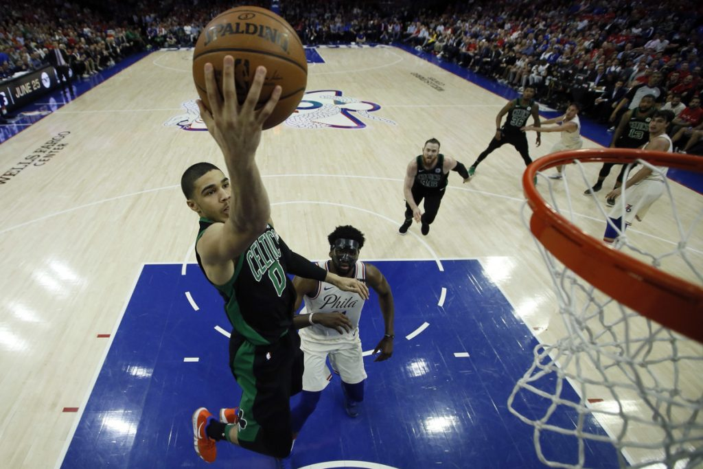 Boston's Jayson Tatum, left, gets past Philadelphia's Joel Embiid and goes strong to the basket.
