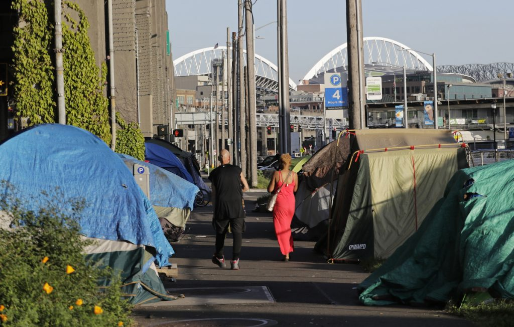 Two people walk past a half-dozen tents set up along a sidewalk at the Seattle waterfront. The city's latest tax proposal would hit Amazon the hardest, requiring employers making at least $20 million in gross revenues to pay $500 a year per worker.