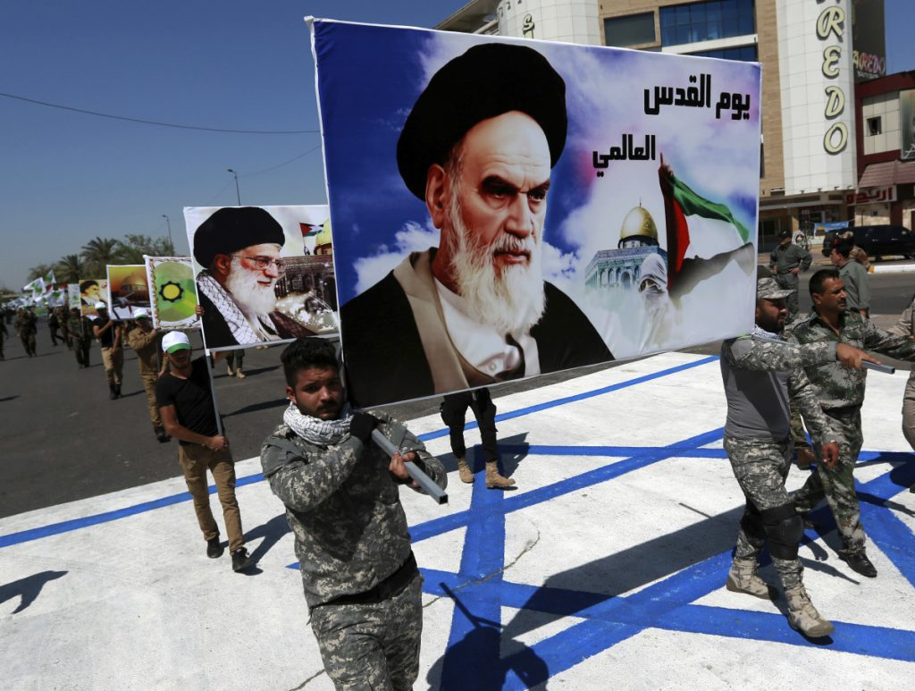 Supporters of Iraqi Hezbollah brigades march on a representation of an Israeli flag with a portrait of late Iranian leader Ayatollah Khomeini and Iran's supreme leader Ayatollah Ali Khamenei, in Baghdad in 2017.