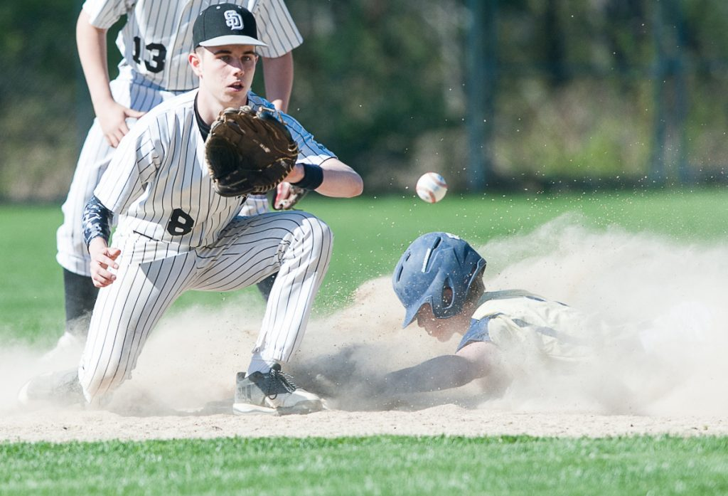 Traip Academy's Charlie Driscoll slides into second with a stolen base, ahead of the tag by Hunter Hughes of St. Dom's. Traip won, 11-2.