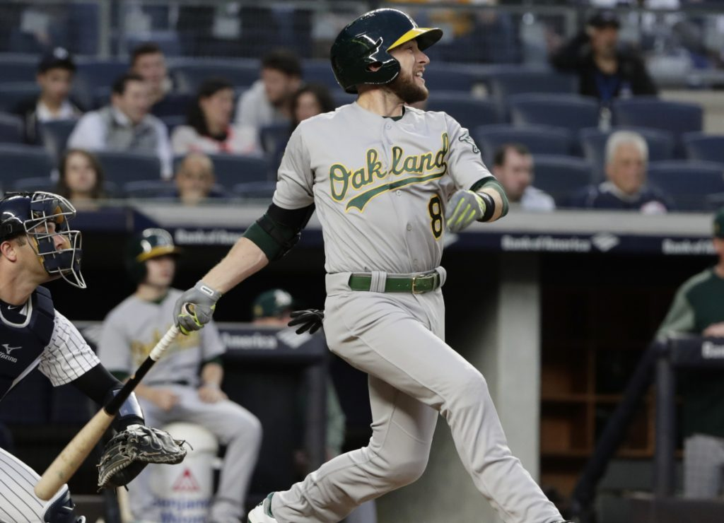 Jed Lowrie of the Athletics watches his RBI single during the third inning of Oakland's 10-5 win over the Yankees on Friday night in New York.