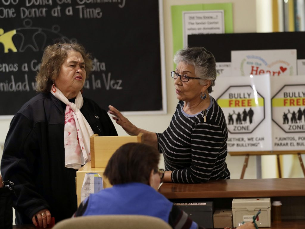 Two women talk in front of anti-bullying signs at the On Lok 30th Street Senior Center in San Francisco. After problems at the facility, staff received 18 hours of training that included lessons on what constitutes bullying and how to manage such conflicts.