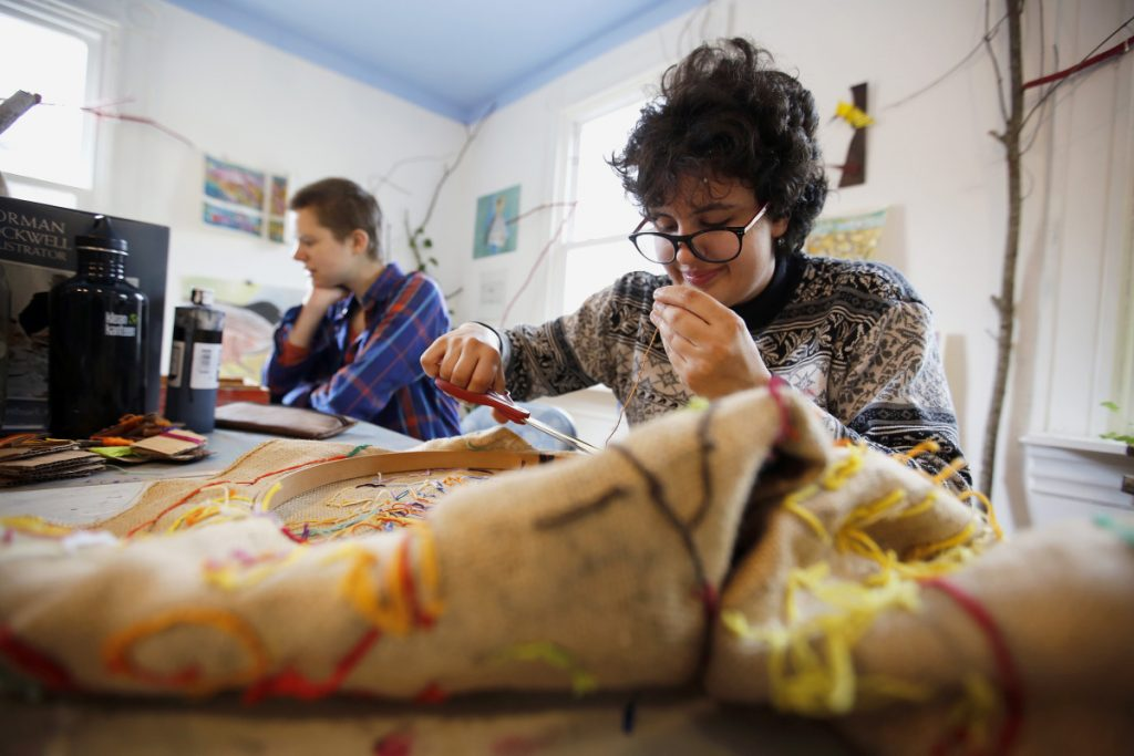 Lidia Woofenden, 21, right, joined by art mentor Julianne Carle, works on a needlepoint design at Spindleworks, a Brunswick arts and crafts studio for adults with intellectual disabilities. A cut in reimbursement rates for MaineCare, effective July 1, has created a looming crisis for group homes as well as day programs like these.