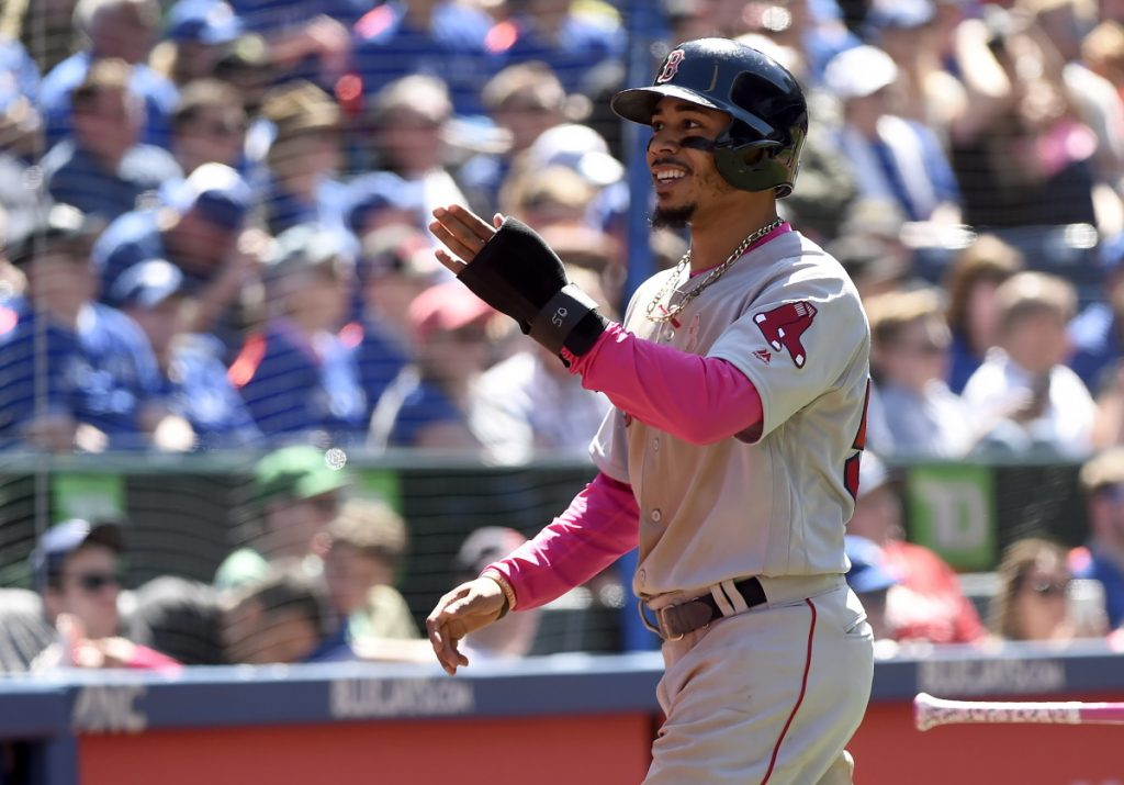Mookie Betts celebrates after scoring in the fifth inning of the Red Sox' 5-3 win over the Blue Jays on Sunday in Toronto.