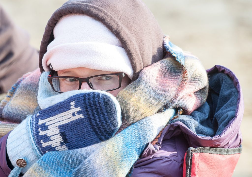 Mandy Hufslader of Dresden keeps bundled up Sunday and watches for a teammate to finish the 100-mile race at Riverlands State Park in Turner.