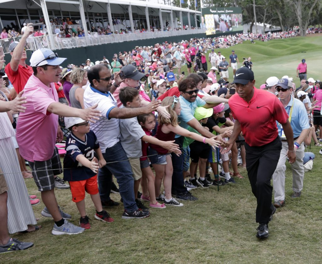Fans greet Tiger Woods as he exits the 18 hole, during the final round of The Players Championship Sunday  in Ponte Vedra Beach, Fla.