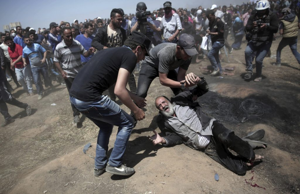 An elderly Palestinian man falls after being shot by Israeli troops during a protest at the Gaza Strip's border with Israel on Monday.