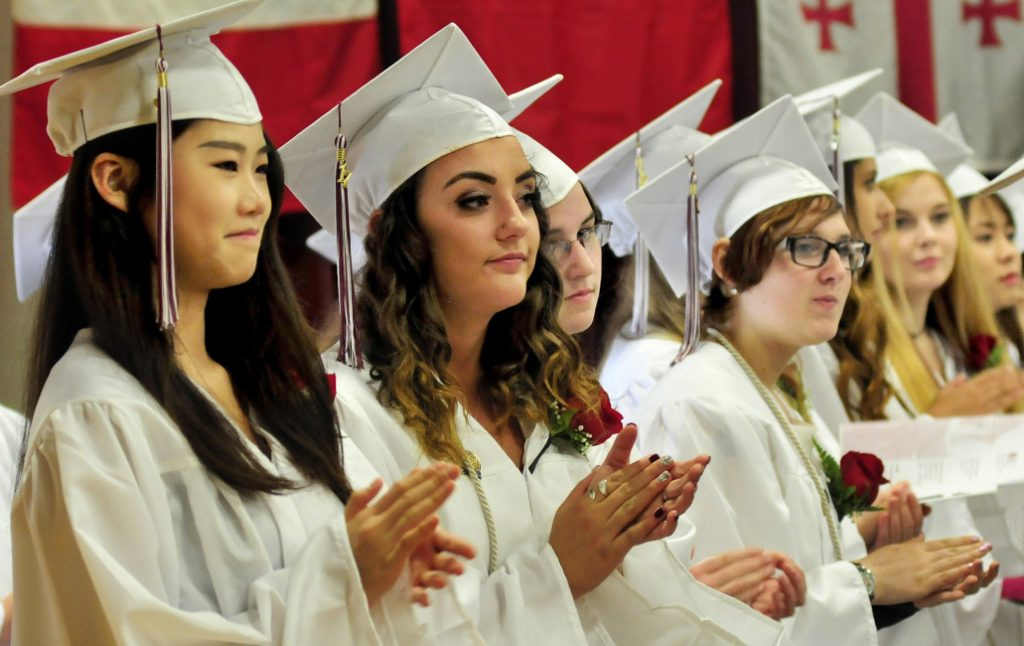 Graduating seniors clap for a classmate during commencement at Maine Central Institute last June 4. The Pittsfield secondary school is reducing its staff because of declining international enrollment.
