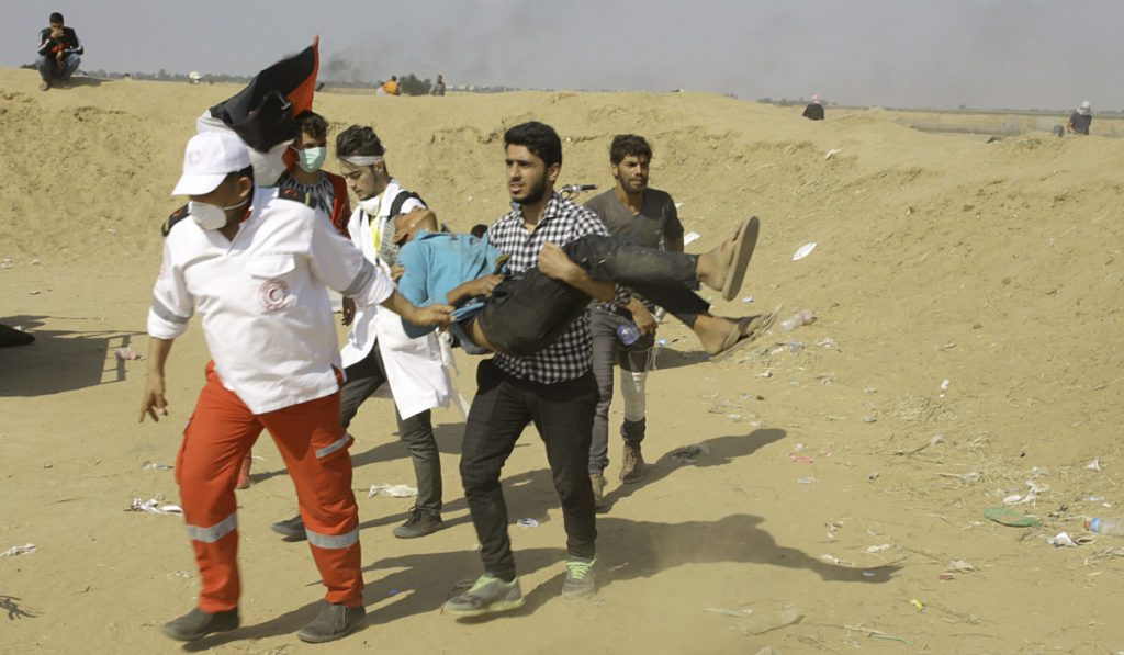 Palestinian medics and protesters evacuate a wounded youth east of Khan Younis in the Gaza Strip on Tuesday. Israel faced a growing backlash Tuesday and new charges of using excessive force, a day after Israeli troops firing from across a border fence killed at least 60 Palestinians and wounded more than 2,700 at a mass protest in Gaza.