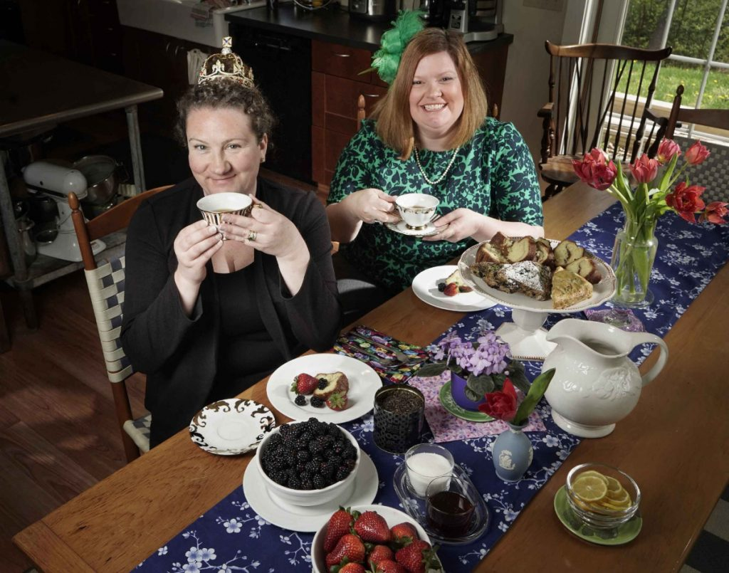 Karen Sigler, left, wearing a crown, and Kristin Fuhrmann-Simmons, wearing a fascinator, with some of the kinds of food and beverages Fuhrmann-Simmons plans to serve at a bash at her home on the morning of the royal wedding.