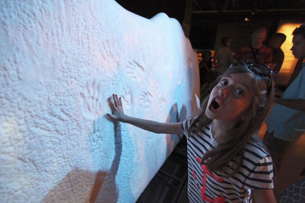 "Dinah Routhier, 9, reacts after placing her hand on a sample ""glacier"" at ""Titanic: The Artifact Exhibition"" at the Portland Science Center."