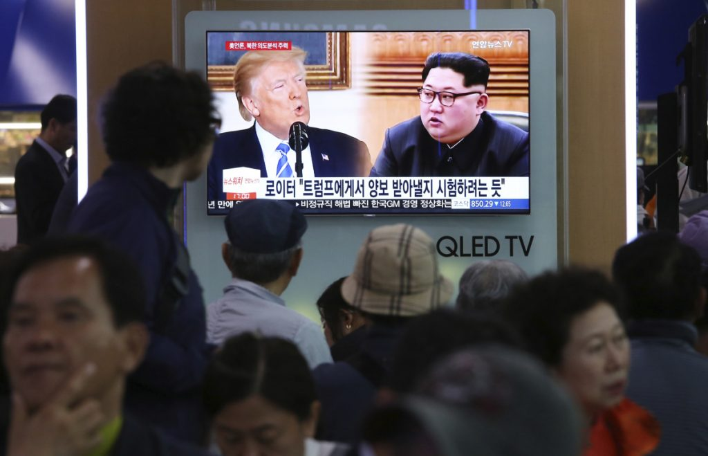 "People watch a TV showing split-screen images of U.S. President Trump and North Korean leader Kim Jong Un during a news program at the Seoul Railway Station in Seoul, South Korea, on Wednesday. North Korea on Wednesday threatened to scrap a historic summit next month between Kim and Trump, saying it has no interest in a ""one-sided"" affair meant to pressure Pyongyang to abandon its nuclear weapons. The signs read: "" Trying to test Trump."""
