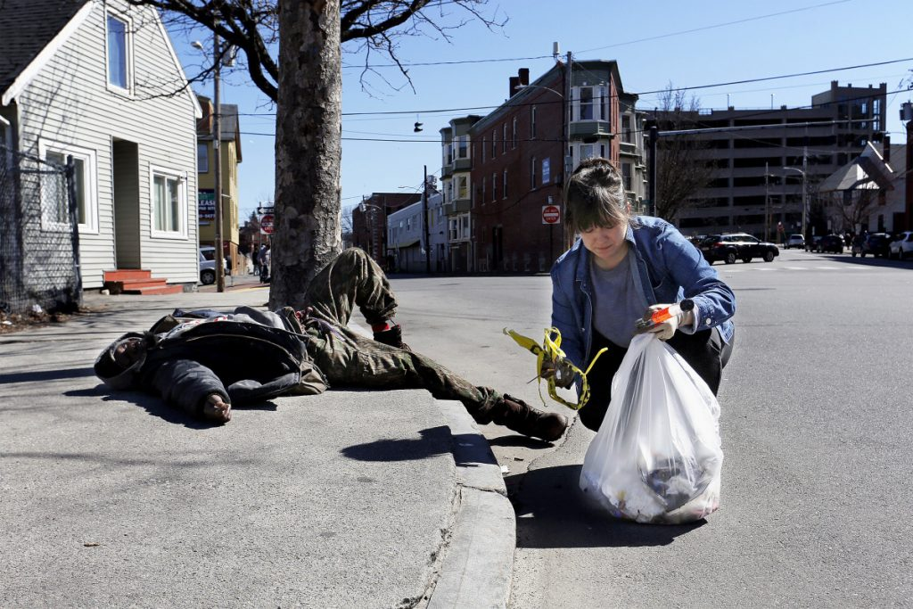 Letter writer Stephanie Scherer, shown picking up litter near an intoxicated man in Bayside, says if other parts of the city had open drug dealing and related violence it would be dealt with immediately.