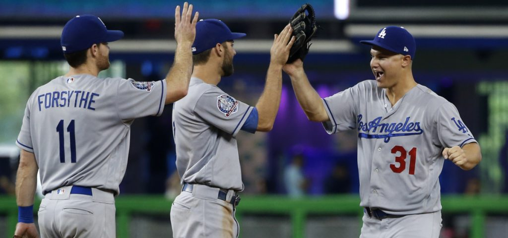 Logan Forsythe, left, Chris Taylor, center, and Joc Pederson celebrate Thursday after the Los Angeles Dodgers – a World Series team a year ago – ended a six-game losing streak by defeating the Miami Marlins, 7-0.