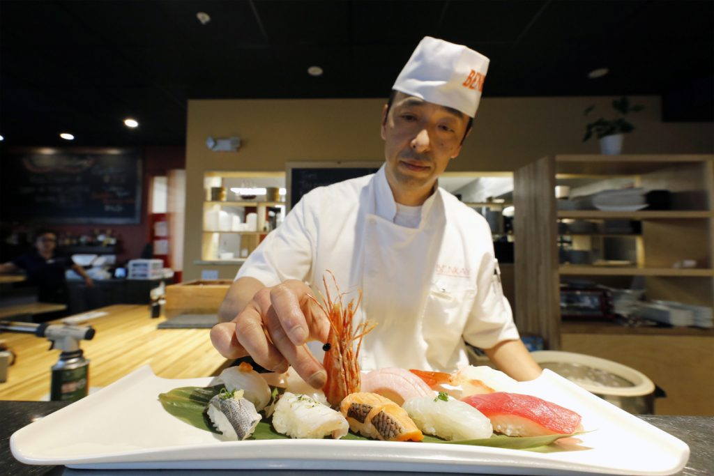 "Benkay sushi chef Hiro Ishii adds a shrimp head as the centerpiece of Omakase – a sushi platter whose name roughly translates to ""chef's choice."""