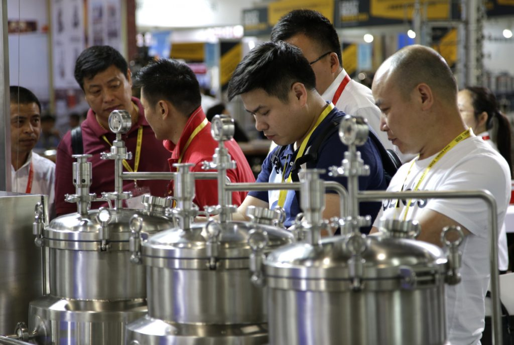 Participants inspect brewing equipment this week at the 2018 Craft Beer of China Exhibition in Shanghai, where brewers networked and shared tips on the latest technologies. A growing middle class in China is shifting from legacy brews to more experimental, refined and expensive beer options.