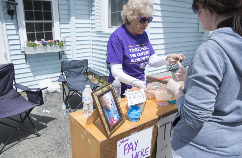 June Conley makes a sale Saturday at her house on Malbons Mills Road in Skowhegan during the area's 10 Mile Yard Sale.