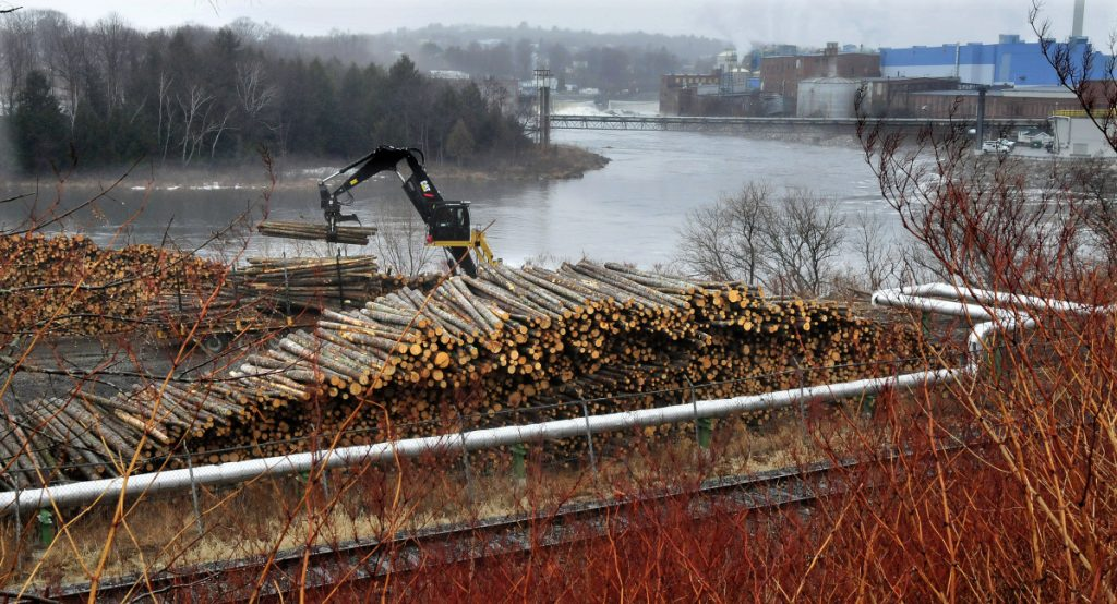 A worker unloads logs in a wood yard in 2016. The logs would be used to make paper at the Madison Paper Industries mill, in the background.