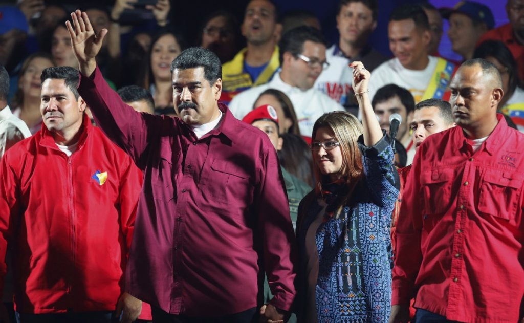 Venezuela's President Nicolas Maduro and his wife Cilia Flores wave to supporters after the National Electoral Council announced that with almost 93 percent of polling stations reporting, Maduro won nearly 68 percent of the votes in Sunday's election.