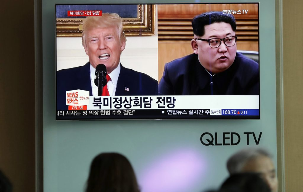 People watch a TV screen showing file footage of U.S. President Trump and North Korean leader Kim Jong Un during a news program at the Seoul Railway Station in Seoul, South Korea. Weeks from his planned North Korea summit, President Trump now says the meeting might not happen.