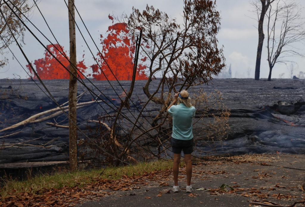 Jim Carpenter photographs lava erupting from fissures in the Leilani Estates subdivision near Pahoa, Hawaii, on Tuesday. The Kilauea volcano lava has destroyed nearly 50 structures.