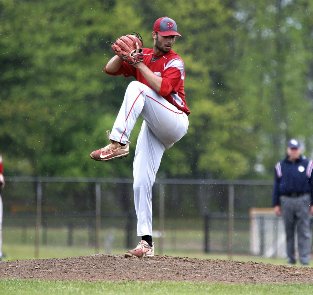 As a persistent rain falls, South Portland pitcher Zach Johnson delivers a pitch against Thornton Academy on Tuesday in Saco. Johnson and the Red Riots beat the Trojans, 9-6.