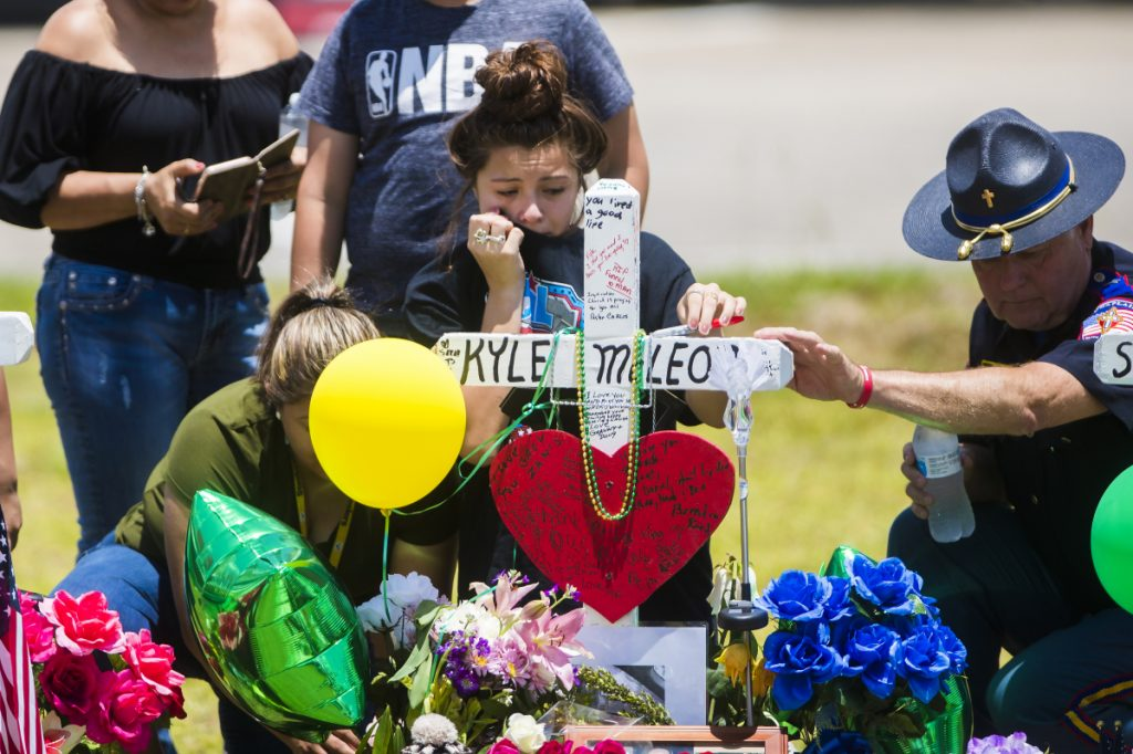 """A young woman cries by a memorial to Santa Fe (Texas) High School shooting victim Aaron Kyle McLeod. Making schools """"more like prisons"""" won't prevent more such tragedies, a reader says."""