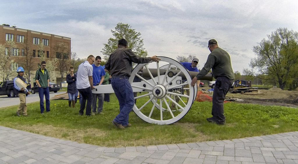 Togus staffers, volunteers and Lewiston Regional Technical Center students and staff roll the new carriage the students built for a Civil War-era 12-pound Napoleon cannon on Thursday at VA Maine Healthcare Systems-Togus campus.