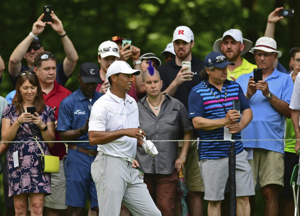 Tiger Woods examines the fairway while spectators take pictures on the ninth hole Thursday during the first round of the Memorial golf tournament in Dublin, Ohio.