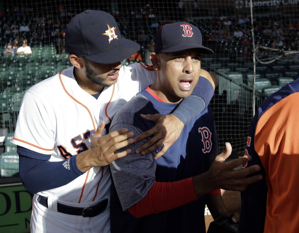 Boston Red Sox manager and former Houston Astros bench coach Alex Cora, right, is hugged by Astros shortstop Carlos Correa after Cora received his 2017 World Series Championship ring before Thursday's game in Houston.