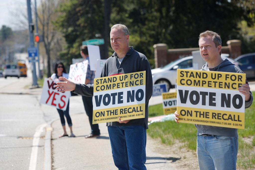"Rodger Kueck, left, and Brent Crossman hold up ""No"" signs to passing traffic on Route 1 as Racquel Undlin and Matt Sither hold ""Yes"" signs. The special election on the recall of three school board members clearly divided the town."