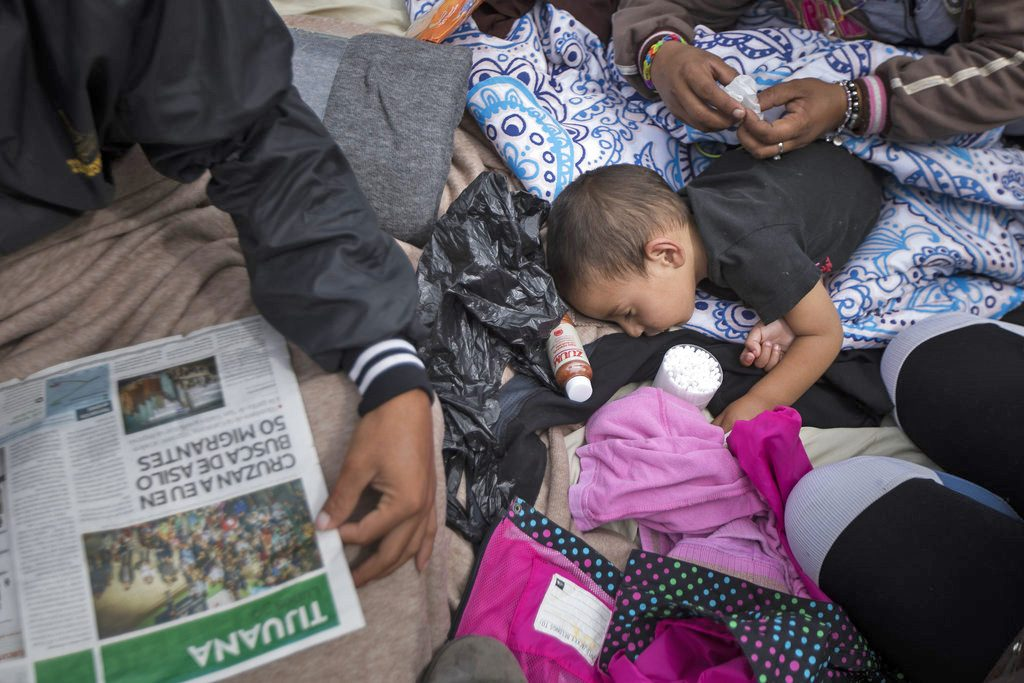 A 2-year-old child from Honduras gets treatment for an ear infection after sleeping in the open in front of the El Chaparral port of entry, in Tijuana, Mexico, Monday. About 200 people in a caravan of Central American asylum seekers waited on the Mexican border with San Diego for a second straight day on Monday to turn themselves in to U.S. border inspectors, who said the nation's busiest crossing facility did not have enough space to accommodate them.
