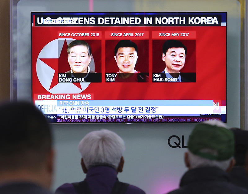 People watch a TV news report screen showing portraits of three Americans, Kim Dong Chul, left, Tony Kim and Kim Hak Song, right, detained in the North Korea, at the Seoul Railway Station in May.