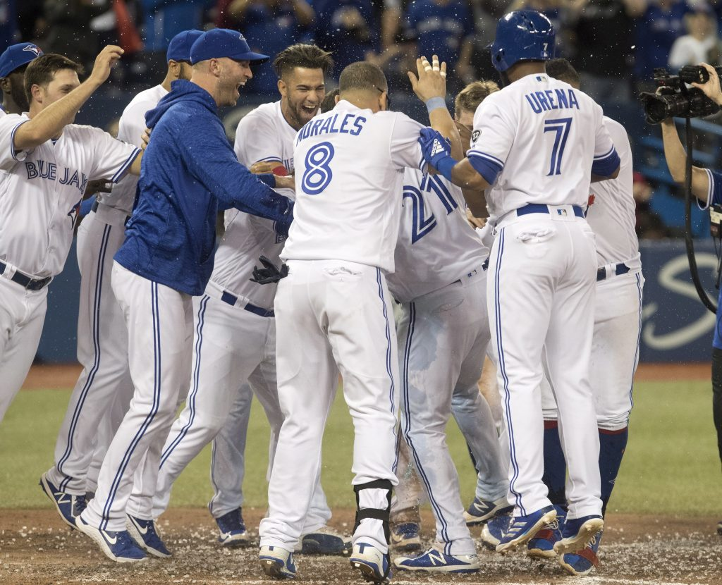 Toronto Blue Jays' Luke Maile is mobbed by teammates after he hit a walkoff home run in the twelfth inning of a baseball game against theBoston Red Sox in Toronto on Friday.
