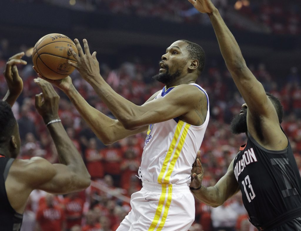 Golden State Warriors forward Kevin Durant (35) drives to the basket past Houston Rockets guard James Harden (13) during the first half of Game 1 of the NBA basketball Western Conference Finals, Monday in Houston.
