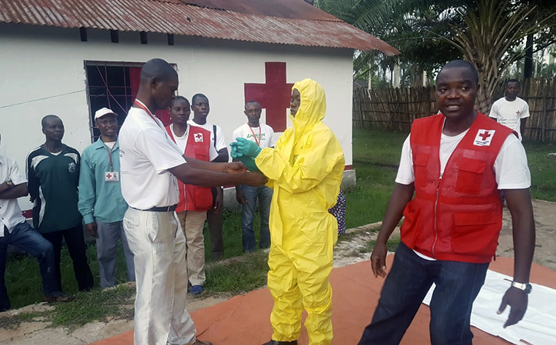 Members of a Red Cross team don protective clothing before heading out to look for suspected victims of Ebola, in Mbandaka, Congo on May 14.