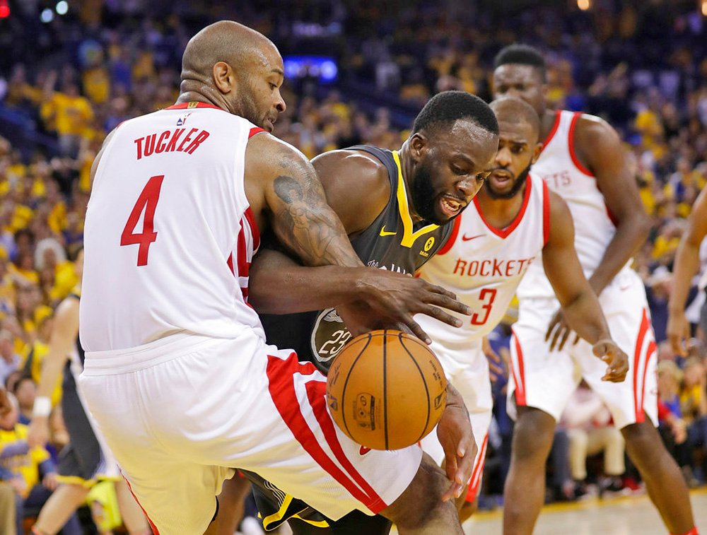 Houston Rockets' P.J.Tucker (4) works for a rebound against Golden State Warriors' Draymond Green, center, during the second half of Game 4 of the Western Conference Finals Tuesday in Oakland, Calif.