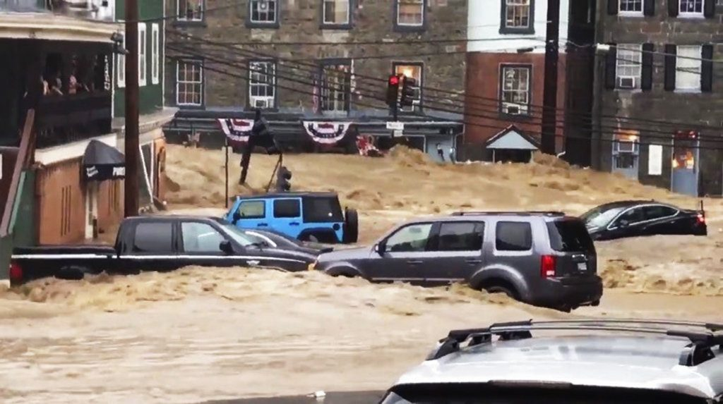 Water rushes through Main Street in Ellicott City, Md., Sunday.     Libby Solomon/The Baltimore Sun